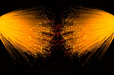 Two illuminated groups of vibrant gold fibre optic strands emanating from the left and right of the image. Black background. photo