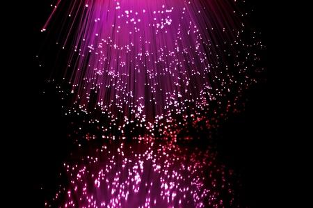 estrellas moradas: Rosa y rojo fibra de hebras luz �ptica reflejando en primer plano.