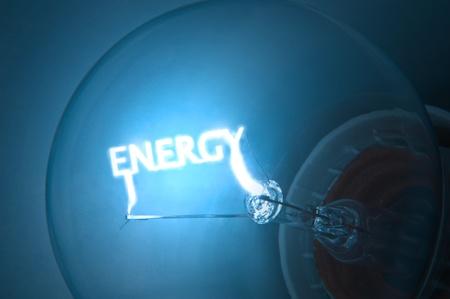 ahorro energia: Cerca de filamento de la bombilla de luz azul iluminada que define la palabra  Foto de archivo