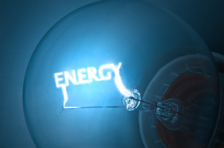 saving electricity: Close up on illuminated blue light bulb filament which spells the word  Stock Photo
