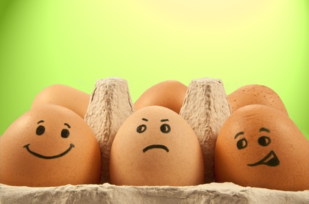humourous: Close and low level of several brown eggs with painted faces against green and yellow light effect background