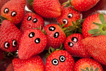 Close up on a group of fresh strawberries with painted eyes depicting different emotions Stock Photo - 8808000