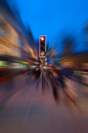 dizzy: A traffic light surrounded by radial motion blur giving a chaotic concept to an evening urban street. Stock Photo