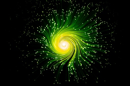 Many illuminated green and yellow fiber optic light strands swirling towards the centre against a black background. photo