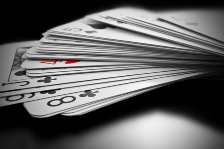 Close up on black and white deck of cards with only one card highlighted with red photo