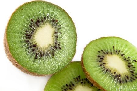 Close up of a partially sliced fresh kiwi fruit arranged over white photo