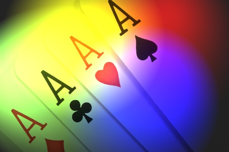achievement cards: Close up of four ace playing cards with multicoloured light effect filter