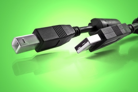 usb2: Close up of two usb cables against green light effect background Stock Photo
