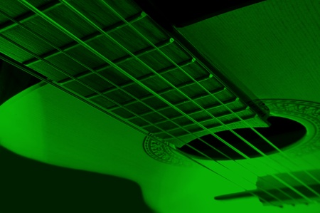 Acoustic guitar with extreme green light effect. photo