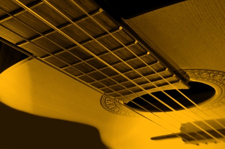 Acoustic guitar with yellow light effect. photo