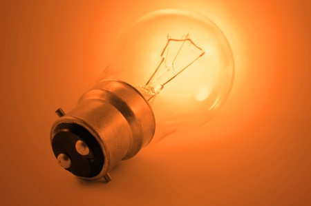 Close up of a single illuminated vibrant orange light bulb Stock Photo - 9098828