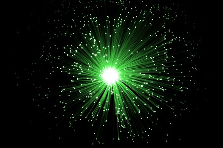 optic: Overhead of illuminated green fiber optic light strands against black background