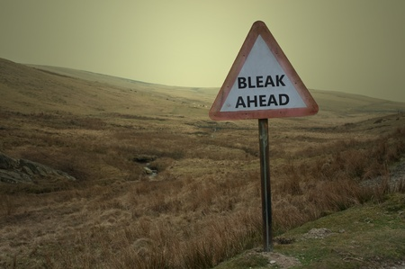bleak: A single weathered British warning road sign with the words bleak ahead against a barren moorland landscape