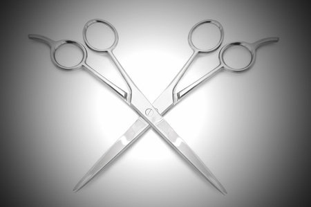 Two stainless steel hairdressing scissors overlapping each other against a white and grey light effect background photo