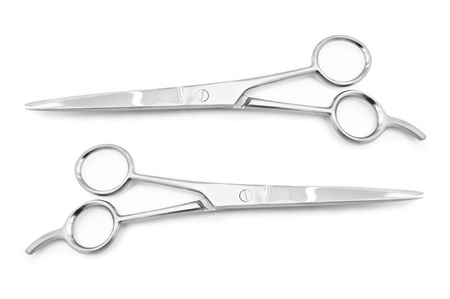 hairdressing scissors: Two sets of stainless steel hairdressing scissors arranged horizontally and parallel to one another over white