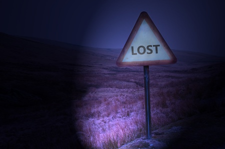 Night shot of a single road warning sign with the word 'lost' illuminated by car headlights with subtle remote and dark landscape behind. Stock Photo - 9266082