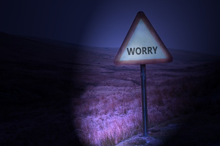 Night shot of a single road warning sign with the word 'worry' illuminated by car headlights with subtle remote and dark landscape behind. Stock Photo - 9266084