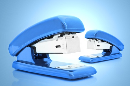 Close up of two blue office staplers isolated over blue light effect photo