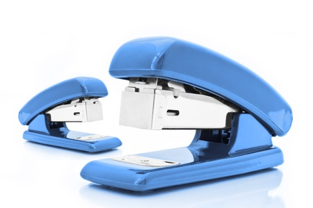 Close up of two blue office staplers isolated over white photo