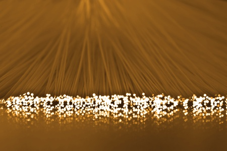 Close up on the ends of many illuminated fibre optic strands which are reflecting into the golden foreground photo