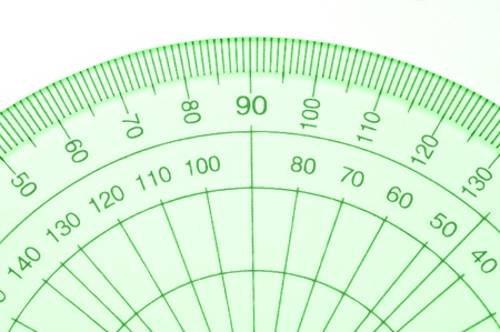 Close Up capturing a portion of a transparent plastic protractor arranged over white. photo