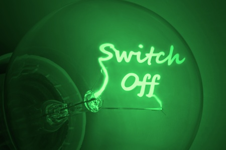 Close up on an illuminated green light bulb filament spelling the words switch off photo