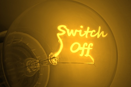saving electricity: Close up of an illuminated yellow light bulb filament spelling the words switch off Stock Photo