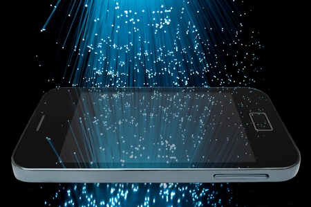 Many illuminated blue fiber optic light strands cascading down against a black background and reflecting on the screen of a smart phone in the foreground Stock Photo - 10010939