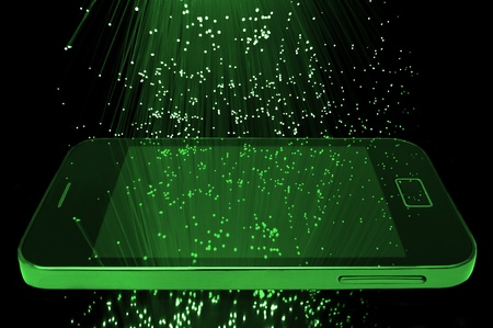 Many illuminated green fiber optic light strands cascading down against a black background and reflecting on the screen of a smart phone in the foreground Stock Photo - 10010936