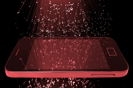 Many illuminated red fiber optic light strands cascading down against a black background and reflecting on the screen of a smart phone in the foreground photo