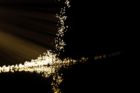 Close up on the ends of golden fibre optic light strands reflecting on black. Stock Photo - 10589102