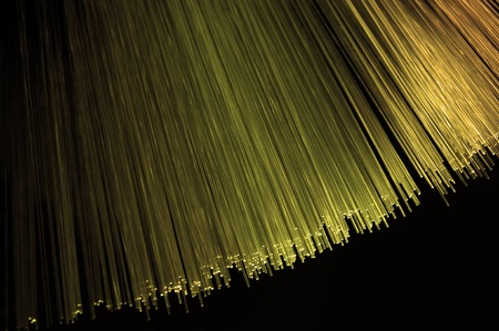 Close up on the ends of many golden illuminated fiber optic light strands arranged over black. Stock Photo - 10589106