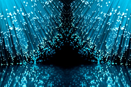 Two groups of blue illuminated fiber optic light strands against a black background and reflecting into the foreground. Stock Photo - 10622584