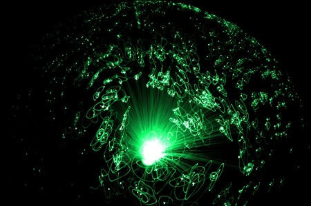 fiber cable: Catching the movement of the ends of many illuminated green fiber optic strands against a black background.