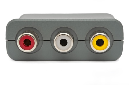 scart: Close up of the jack sockets on a grey scart adapter block arranged over white. Stock Photo