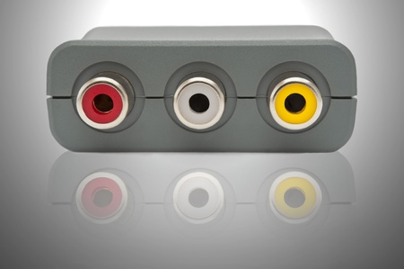 Close up on the outlets of a single scart adaptor block arranged over grey and white light effect and reflecting into the foreground. Stock Photo - 10654251
