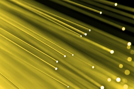 Close up on the ends of a selection of illuminated yellow fiber optic light strands with black background. photo