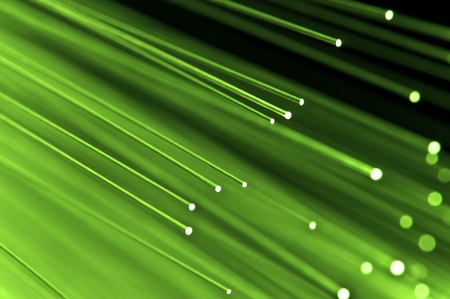 Close up on the ends of a selection of illuminated light green fiber optic light strands with black background.
