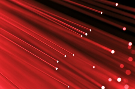 Close up on the ends of a selection of illuminated red fiber optic light strands with black background. Stock Photo - 10851154