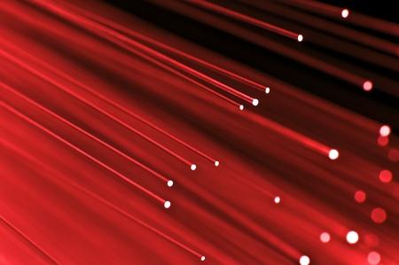 Close-up op de uiteinden van een selectie van verlichte rode glasvezel licht strengen met zwarte achtergrond.
