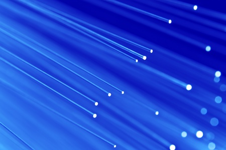 optic: Close up on the ends of a selection of illuminated blue fiber optic light strands with blue background.