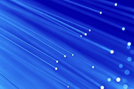 fiber cable: Close-up op de uiteinden van een selectie van verlichte blauwe glasvezel licht strengen met blauwe achtergrond. Stockfoto