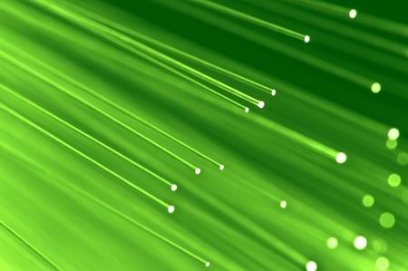 optical fiber: Close up on the ends of a selection of illuminated light green fiber optic light strands with green background.