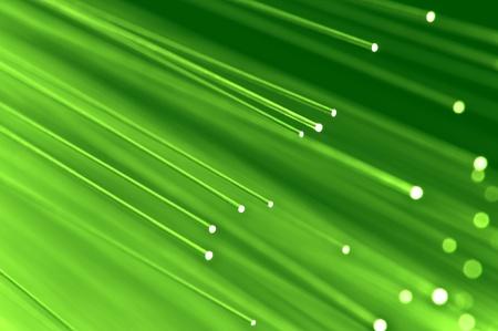 fiber cable: Close-up op de uiteinden van een selectie van verlichte lichtgroen glasvezel licht strengen met groene achtergrond.