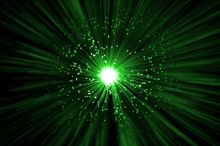 The ends of many illuminated green fibre optic strands emitting a green light blur effect from the centre against a dark background. Stock Photo