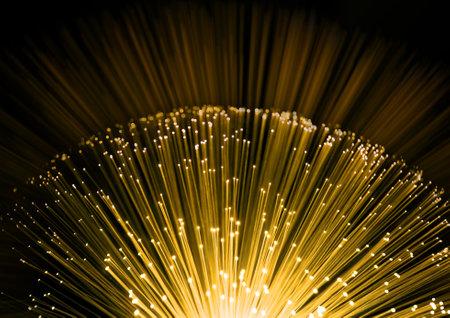fibra óptica: Cerca de los extremos de muchas hebras de fibra óptica iluminada con un fondo borroso negro y amarillo. Foto de archivo