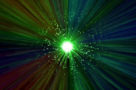 fiberoptics: The ends of many illuminated green fibre optic strands emitting a multicoloured light blur effect from the centre against a dark background. Stock Photo