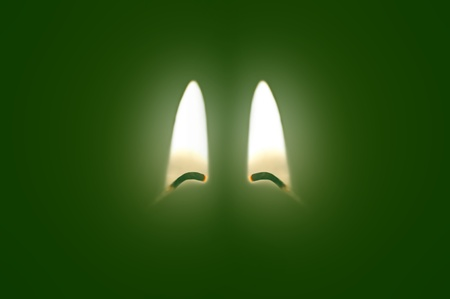 Close up on two ignited candle wicks against a green background. Stock Photo - 11103965