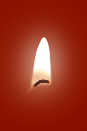 Close up on a single ignited candle wick against a red background. Stock Photo - 11104567