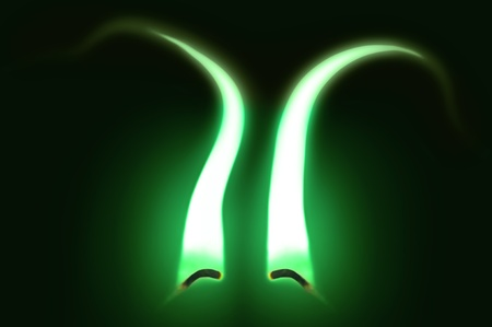 Close up on two ignited candle wicks with green extended flames against a black background. Stock Photo - 11104568